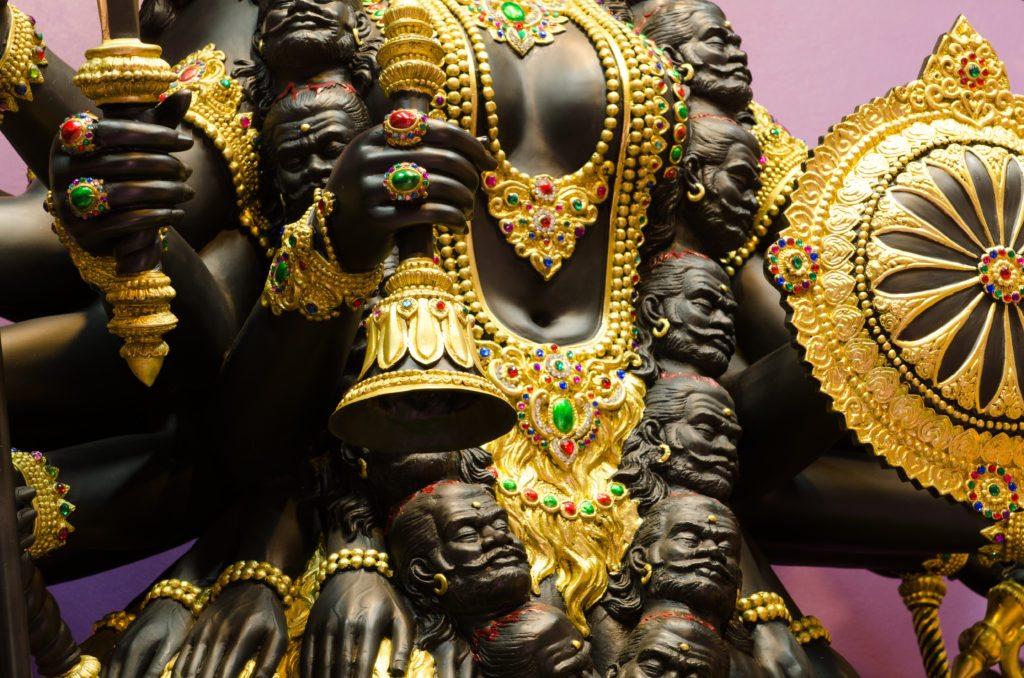 Bell in hand of Kali statue inside ashram at thailand