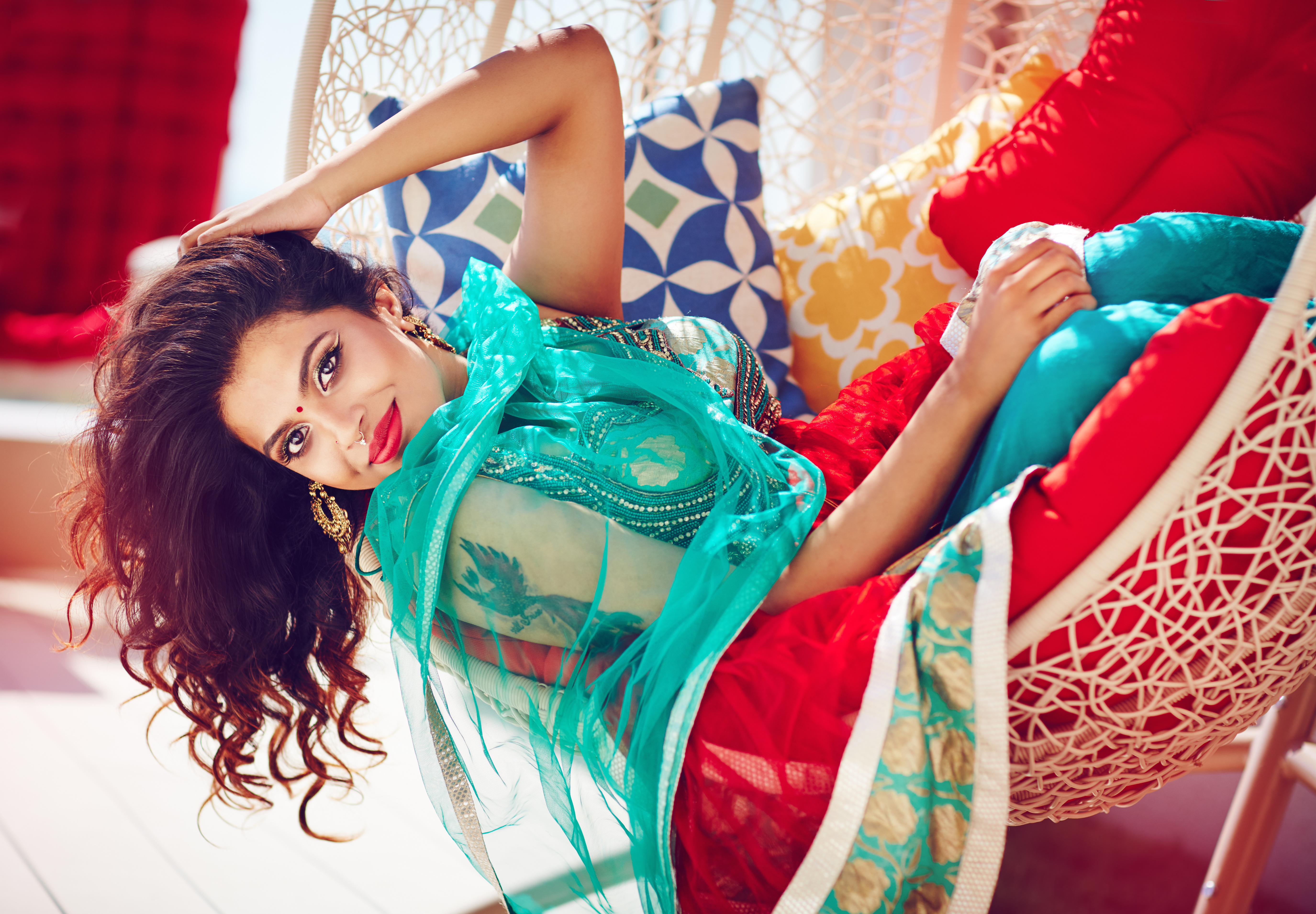 beautiful indian woman in traditional dress relaxing on sofa
