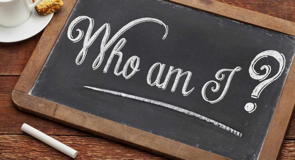 Who am I ? A philosophical question  on a vintage blackboard with white chalk with a cup of coffee
